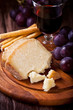 Pecorino with Red Grapes and Wine on Wooden Board