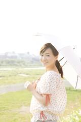 日傘を持って振り返る女性