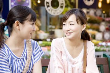 ベンチに座って会話する女性2人
