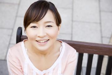 ベンチに座って微笑む女性