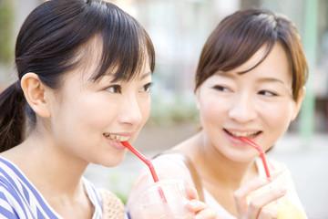 屋外でジュースを飲む女性2人