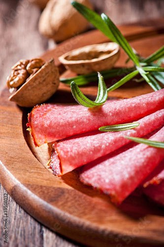 Spicy Salami with Rosemary on Wooden Board