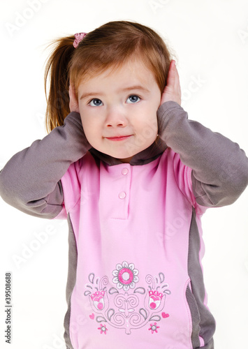 Portrait of little girl covering her ears with hands