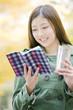 公園で飲み物を持ちながら読書する女性