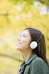 銀杏を見上げながらヘッドホンで音楽を聴いている女性