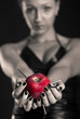 Conceptual image of beautiful girl with nails driven apple.