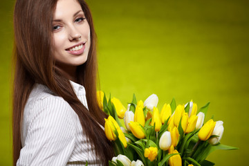 Smiling girl with yellow tulips. green background