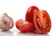 Frische Tomaten mit Knoblauchzwiebel vor weißem Hintergrund