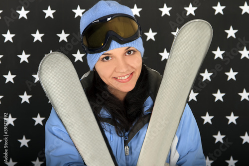 Happy girl with ski in the winter sportwear