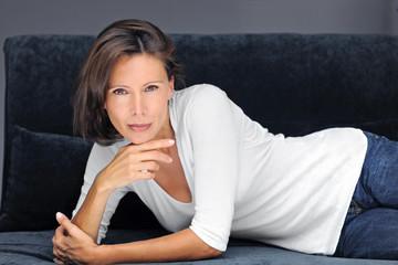 femme brune sur canapé noir