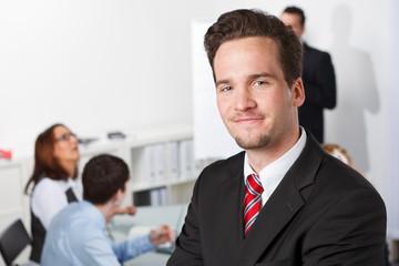attraktiver mitarbeiter steht vor seinen kollegen