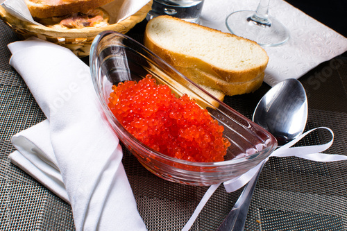 Red caviar in a glass plate next to the bread