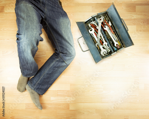 plumber lying on floor with toolbox