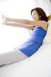 ベッドの上に座り伸びをする女性