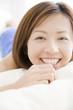 ベッドの上でうつ伏せになり笑っている女性