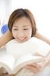 ベッドの上でうつ伏せになり本を読んでいる女性