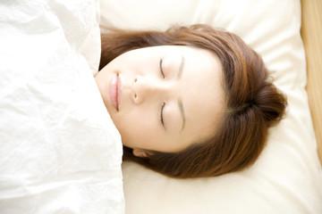 ベッドであお向けに寝ている女性