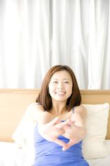 ベッドの上に座り伸びをしている女性