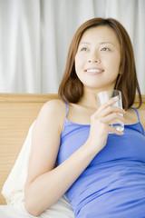 ベッドの上に座り水を飲む女性