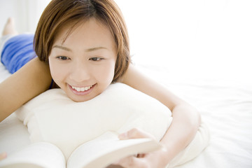 ベッドの上でうつ伏せになり本を読む女性