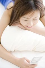 ベッドの上でうつ伏せになり携帯電話のメールを確認している女性
