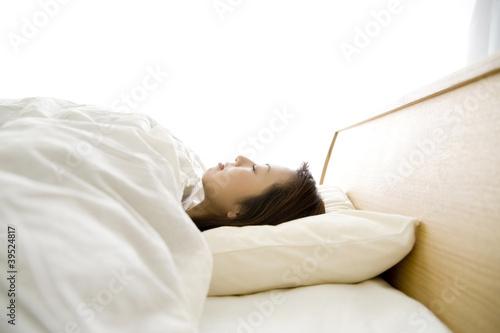 ベッドで仰向けに寝ている女性