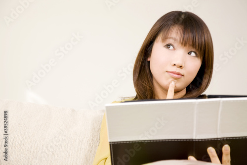 ソファに座り本を見ながら考え事をしている女性