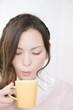ホットコーヒーを冷ましている女性
