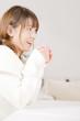 マグカップを持ちながら笑っている女性