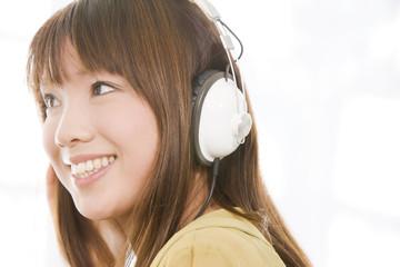 ヘッドホンで音楽を聴いている女性