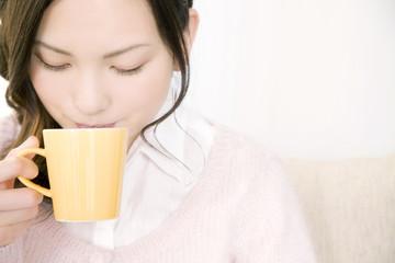 ソファに座りながらホットコーヒーを飲む女性