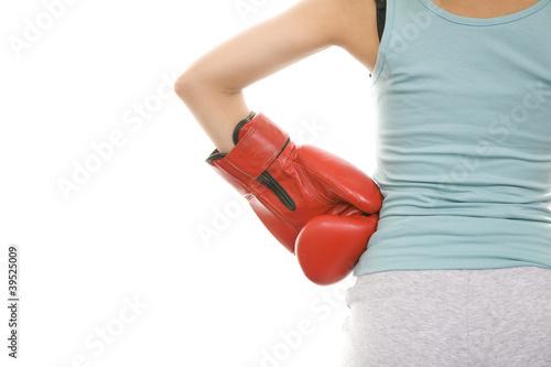 ボクシンググローブをはめた手を腰に当てる女性の後ろ姿
