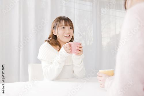 飲み物を飲みながら友達と談笑している女性
