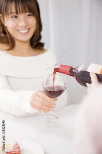 ワインを友達に注いでもらっている女性