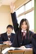 挙手をする女子中学生
