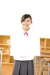 教室でメッセージボードを持っている女子中学生