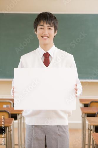 教室でホワイトボードを持つ男子中学生