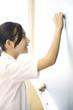 教室の黒板に解答を書く女子中学生