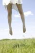 芝生の上でジャンプする女性の足元