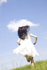 草原を走っている女性の後ろ姿