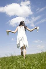 草原を歩く女性の後ろ姿