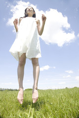 芝生の上でジャンプする女性