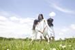 草原で輪になり遊ぶ女の子2人と若い女性