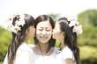 若い女性の頬にキスをする2人の女の子