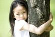 木に抱きつく女の子