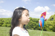 風車に息を吹きかける女の子