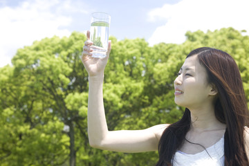 グラスに入った水を見ている女性