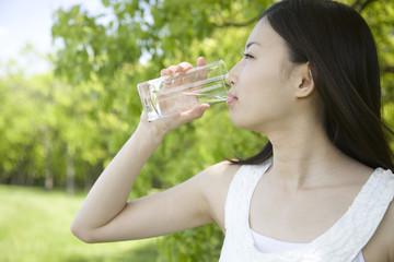 グラスで水を飲む女性