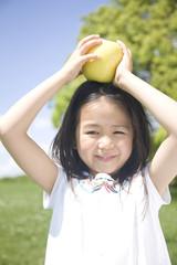 青リンゴを頭にのせている女の子