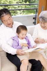 孫息子に絵本を読み聞かせる祖父母
